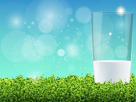 milk drop: glass of milk on the green grass