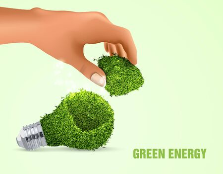 green light bulb: light out of the grass with a hand and highlights  the concept of clean energy
