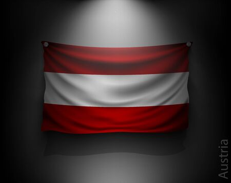 austria: waving flag austria on a dark wall with a spotlight, illuminated