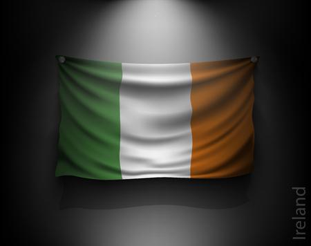 irish history: waving flag ireland on a dark wall with a spotlight, illuminated