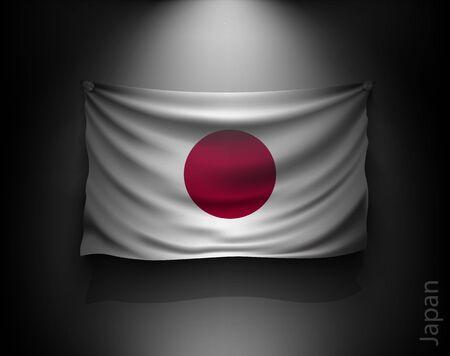 japan flag: waving flag japan on a dark wall with a spotlight, illuminated