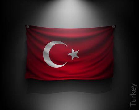 agitant un drapeau de dinde sur un mur sombre avec un projecteur, éclairé