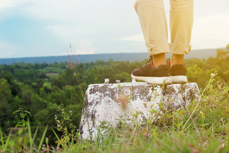Woman jeans and sneaker shoes walking on the Stone road on the summer season nature on background.Getting Started, Decision Making Standard-Bild