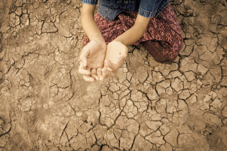 Sad kid despair sitting on cracked earth on hot and dry empty land. Affected of global warming made climate change. Water shortage and drought concept.