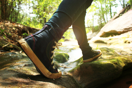 Traveller feet in sneakers surrounded at natural beauty, concept travel, color of vintage tone and soft focus. Stock Photo