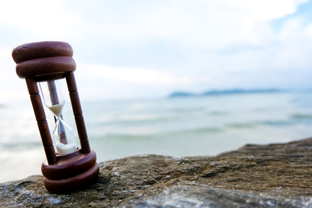 Hourglass on a sand dune beach. Beach and sea background, concept for vacation countdown. Imagens