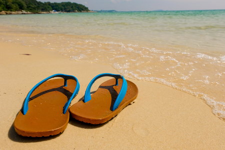 Beach sandals on the sandy sea, Summer concept with sandy beach. Vacation travel icon.