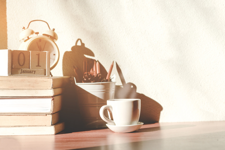 Stack old books with a cup of freshly coffee, vintage alarm clockon, wooden calendar, on table in sunlight morning, Start up concept. Reklamní fotografie