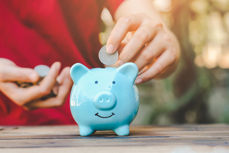 Hand putting coin into piggy bank, Saving and investment money for prepare in the future - Saving money concept.