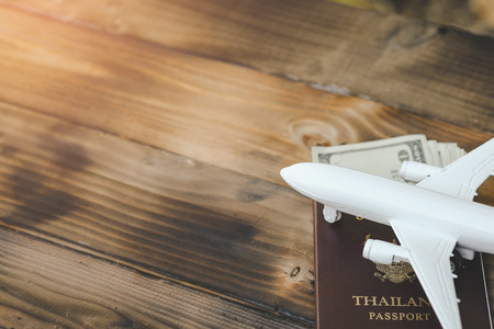 White model of passenger plane with passport and money on old wooden background. Travel saving and planning concept - Top view.