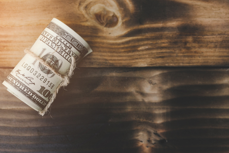 Roll of one hundred dollars banknotes on a old wooden table. Save and investment money for prepare in the future - Saving money concept.