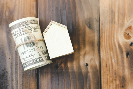 Model house, Roll of one hundred dollars banknotes on a old wooden table. Save and investment money for prepare in the future - Saving money concept. 스톡 콘텐츠