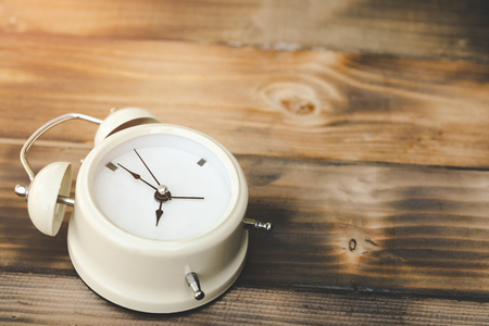 Alarm clock showing almost 12 o clock, on old wooden floor background - Time concept. 스톡 콘텐츠