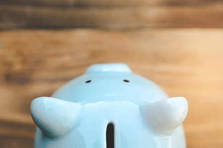 Blue piggy bank on old wooden floor. ideas about saving money for future use - business success concept. 스톡 콘텐츠