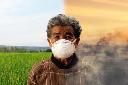 old woman wearing face mask because of air pollution city with Dense smoke pollutes the air and view of a field with a cloudy blue sky clean atmosphere in the background. comparison of clean city and