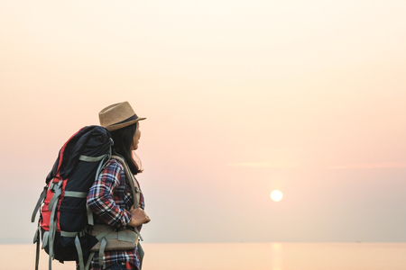 Tourist woman relaxing alone with a large backpack enjoying in lake view. Travel wanderlust lifestyle concept adventure vacations outdoor, Summer holiday and vacation trip