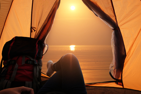 Feet of young women relaxing with lake view from tent camping entrance outdoor. Travel wanderlust lifestyle concept adventure vacations outdoor, Summer holiday and vacation trip