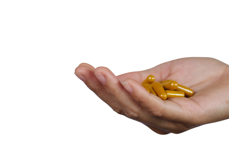 Medicine pills or capsules in hand - isolated on white background with clipping path.