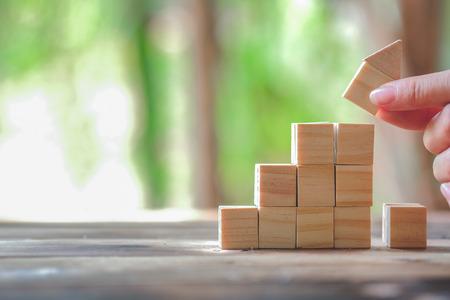 Houtblok stapelen als stap trap en munten gestapeld, bedrijfsgroei tot succes. Opstartconcepten met bedrijfsstrategiesymbolen op houten kubussen - Risicobeheer.