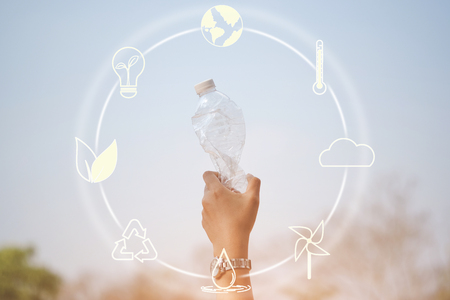 Hand holding plastic bottle on blue sky with icons about environment on image - concept of environmentally friendly with recycling.