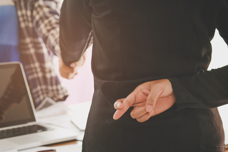 Business people shaking hands and one of them holding fingers crossed behind back, Represents the betrayal.