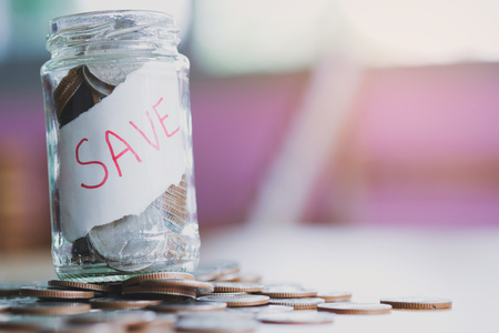saving money with hand putting coins in jar glass, save and investment money for prepare in the future - saving financial concept
