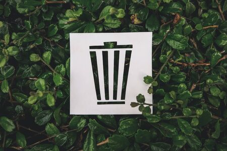 Trash icon created with paper cut on green leaves background, Concept of environmental conservation and protection.
