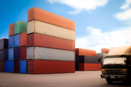 Stack of containers box in a logistic depot yard and track head without labels on blue sky backdrop. Cargo freight ship for import export. Free space for text.