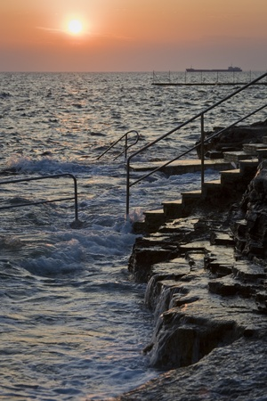 Sunset and flow on the rocky beach