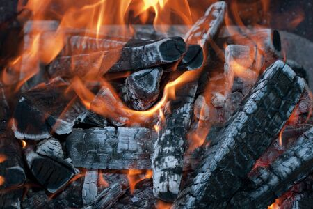 Middle of a wood fire with flames and glowing embers, close up  photo