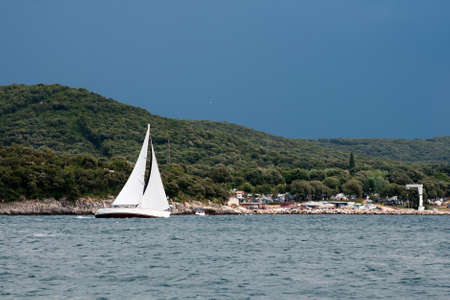 Luxury sail yacht at famous Limsky canal before thunderstorm. Adriatic sea. Croatia.