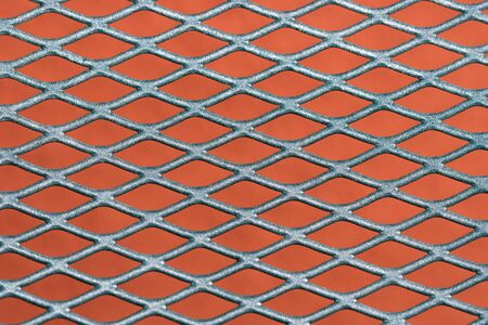 Abstract metal grating against red wall background Stock Photo