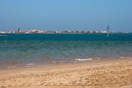 エジプトの紅海の砂浜ビーチ沿いをウィンド サーフィン
