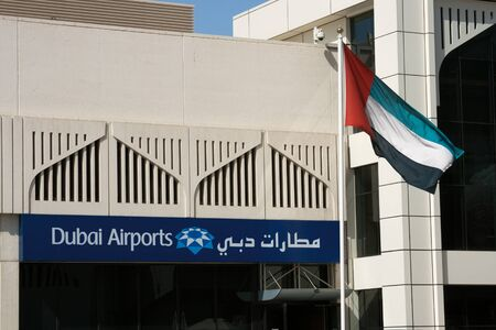 dubai flag: Dubai, Inited Arab Emirates - May 24, 2011 - A sign above the international departure terminal at International Airport in Dubai and national UAE flag.