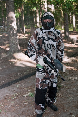 Teen paintballer with a gun wearing protective mask