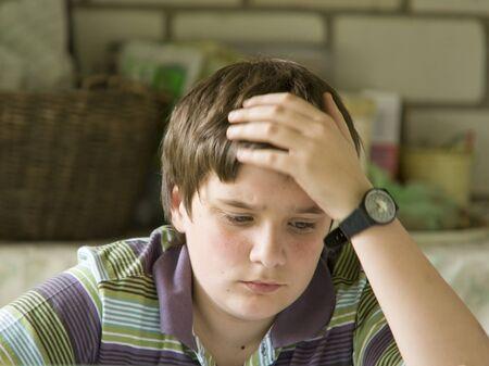 Thinking boy hardly solving homework photo