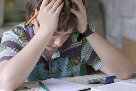 Thinking boy hardly solving homework Stock Photo - 11089355