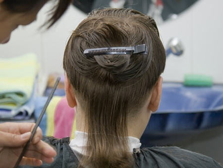 slicked back hair: Boy having a hair cut at the hairdressers