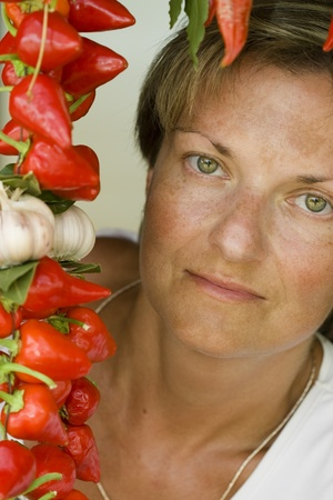 Colorful portrait of tanned woman with green eyes and red pepper. photo