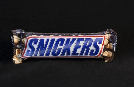 Kiev, Ukraine - April 09, 2011: Snickers chocolate bar against black background in Kiev, Ukraine.