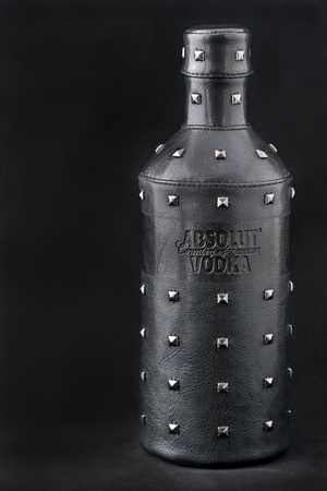 Kiev, Ukraine - June 05, 2011: Absolut Vodka Rock Edition bottle with black leather cover against black background in Kiev, Ukraine. Stock Photo - 12280330