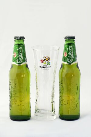 carlsberg: Kiev, Ukraine - April 30, 2012: Two Carlsberg beer bottles and empty glass with official logotype of UEFA Championship EURO 2012 Poland-Ukraine against white background. Editorial