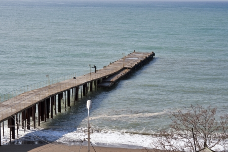 Sea pier and lonely fisherman. Sudak, Crimea. photo