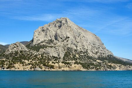 rocky mountain juniper: Sokol (Falcon) mountain in Crimea, Ukraine. Favorite place for rock climbers. Rocky coastline on blue sky background. Noviy Svet nature reserve.