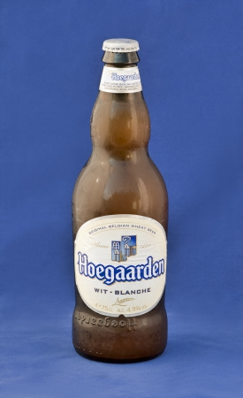 Hoegaarden wheat Belgian beer cold bottle against blue background. The Belgian village of Hoegaarden had been known for its white beers since the Middle Ages. Hoegaarden wheat Belgian beer first brewed in 1445 is spiced with coriander and orange peel. It