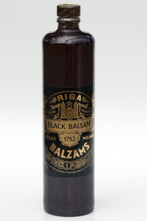 balsam: Herb hard liqueur Riga Black Balsam bottle against white background. Riga Black Balsam is a traditional Latvian herbal liqueur made with many different natural ingredients mixed in pure vodka, 45% drink. The traditional recipe was created by pharmacist Ab Editorial