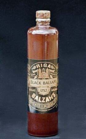 balsam: Herb hard liqueur Riga Black Balsam bottle against black background. Riga Black Balsam is a traditional Latvian herbal liqueur made with many different natural ingredients mixed in pure vodka, 45% drink. The traditional recipe was created by pharmacist Ab Editorial