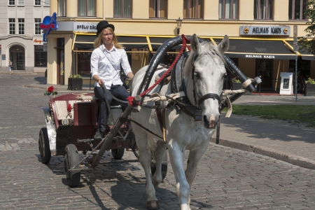 Riga, Latvia - July 27, 2012: Woman horse carriage on a Riga city street in Latvia.