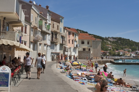 BASKA, CROATIA - AUGUST 09: People walk, sunbathe and swim on the seafront and beach of mediterranean town of island Krk on August 09, 2012 in Baska, Croatia. Baska Voda is a municipality in the Split-Dalmatia County.