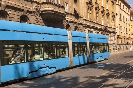 ZAGREB, CROATIA - AUGUST 21: Pedestrians walk along city street with old houses and passengers travel by tram in Zagreb, Croatia on August 21, 2012.
